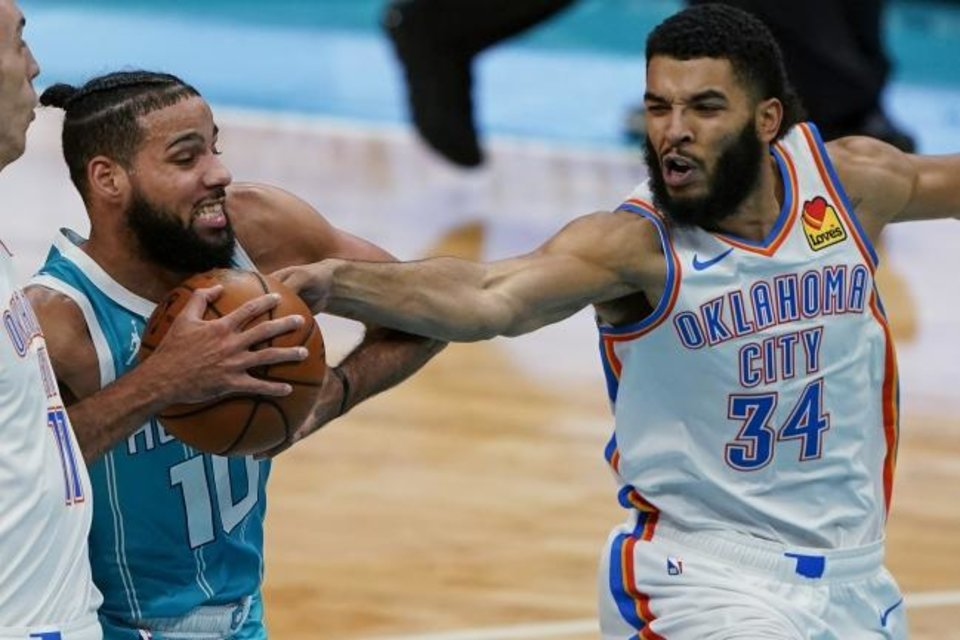 Photo -  Thunder forward Kenrich Williams, right, tries to swipe the ball away from Hornets forward Caleb Martin on Dec. 26 in Charlotte, N.C. [AP Photo/Chris Carlson]