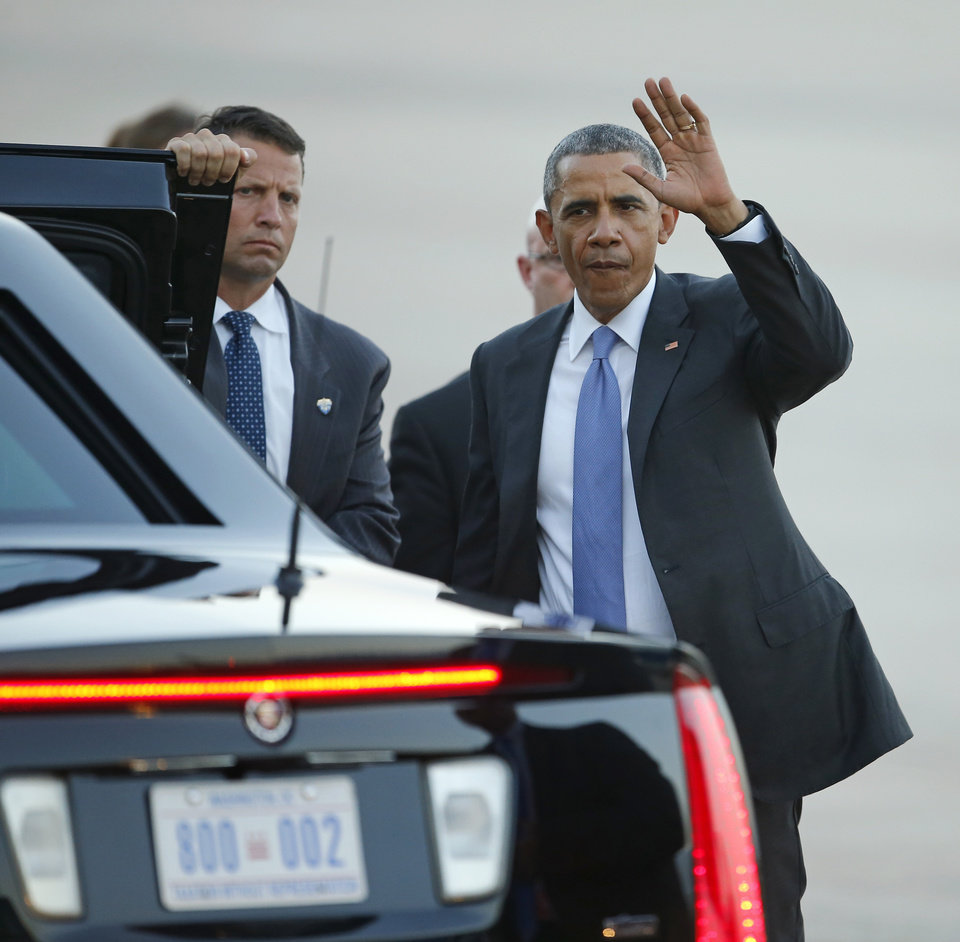 Photo - President Barack Obama waves to the crowd before getting in his car after arriving on Air Force One at Tinker Air Force Base in Midwest City, Wednesday, July 15, 2015. President Barack Obama will visit the Federal Correctional Institution El Reno, where he will meet with Oklahoma law enforcement officials and inmates and conduct an interview for a documentary scheduled to air in the fall. Photo by Bryan Terry, The Oklahoman