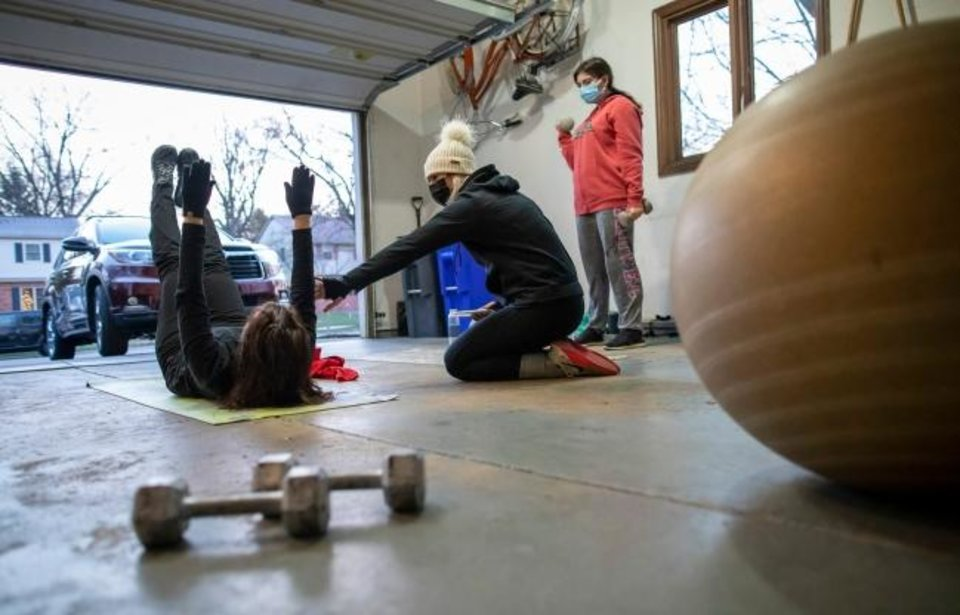 Photo -  Olga Stavridis, 53, left, and her daughter, Maria Stavridis, 21, right, work out with personal trainer Caitlin Kennelly in the garage of Donna Reda's Upper Arlington, Ohio, home. [Adam Cairns/Columbus Dispatch/TNS]
