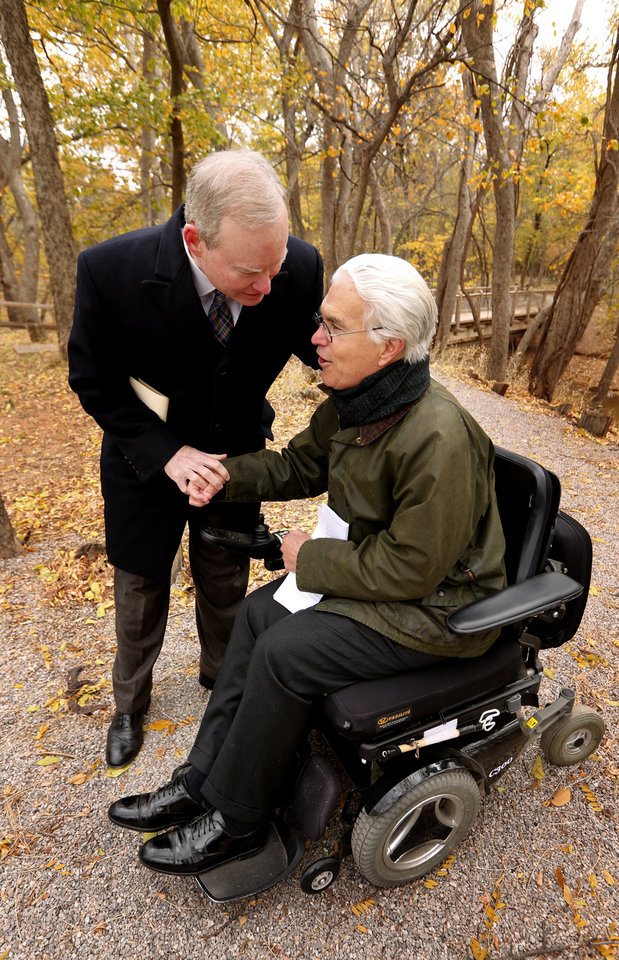 Photo - Wilderness Matters Co-Founder Jack McMahan is congratulated by Mayor Mick Cornett as they hold a ceremony to mark the beginning of an effort to remove barriers to accessibility at Martin Park Nature Center on Wednesday, Nov. 12, 2014, in Oklahoma City, Okla.  Photo by Steve Sisney, The Oklahoman