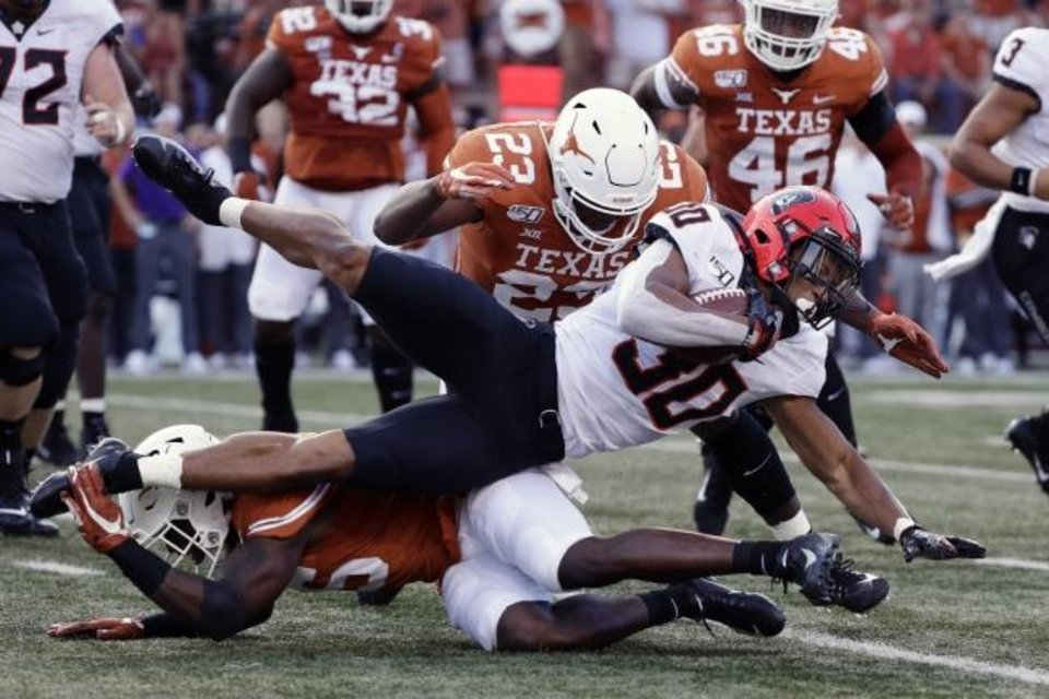 Photo -  Oklahoma State running back Chuba Hubbard (30) is stopped by Texas defensive lineman Peter Mpagi, bottom, and linebacker Jeffrey McCulloch (23) during the first half Saturday in Austin, Texas. [AP Photo/Eric Gay]