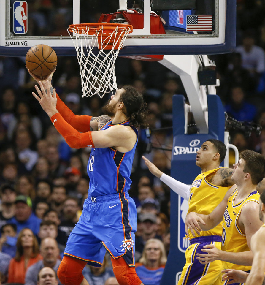 Photo - Oklahoma City's Steven Adams (12) shoots in front of Los Angeles' Kyle Kuzma (0) and Ivica Zubac (40) in the fourth quarter during an NBA basketball game between the Los Angeles Lakers and the Oklahoma City Thunder at Chesapeake Energy Arena in Oklahoma City, Thursday, Jan. 17, 2019. Los Angeles won 128-138 in overtime. Photo by Nate Billings, The Oklahoman
