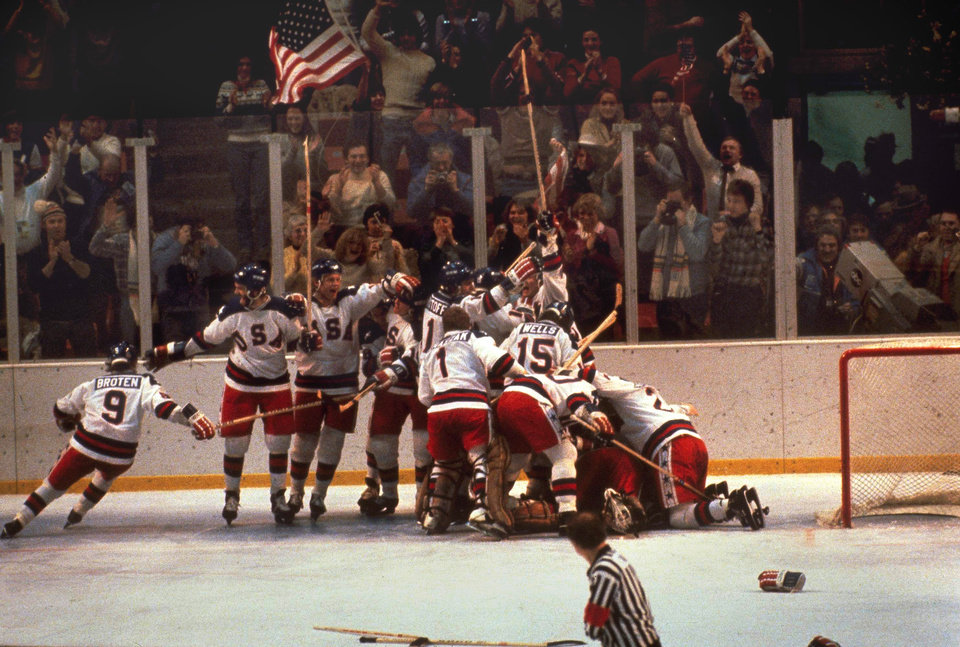 Photo -  The U.S. hockey team pounces on goalie Jim Craig after a 4-3 victory against the Soviets in the 1980 Olympics. [AP PHOTO]