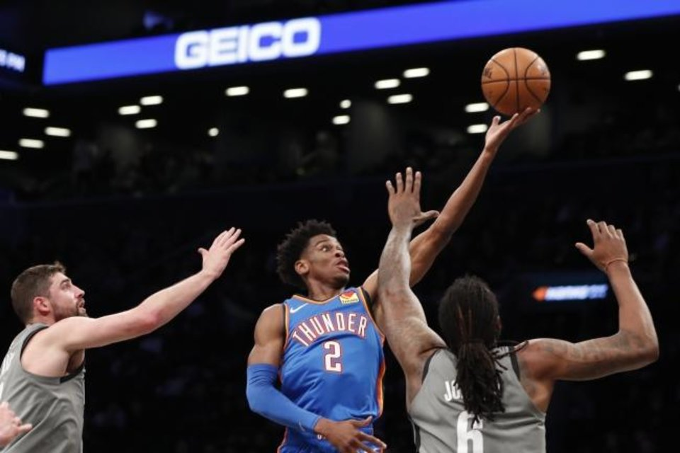Photo -  Oklahoma City Thunder guard Shai Gilgeous-Alexander (2) goes up for two points as Brooklyn's Joe Harris, left, and DeAndre Jordan defend during Tuesday night's game in New York. OKC beat the Nets 111-103 in overtime. [AP Photo/Kathy Willens]
