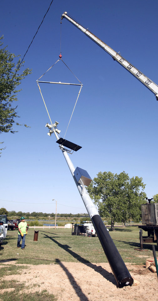 Photo - A new siren is installed at Eagle Lake in Del City on Wednesday. Del City is installing eight new sirens around town. Photos by Paul B. Southerland, The Oklahoman