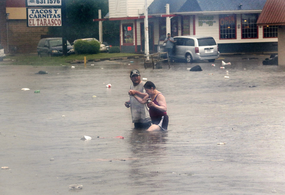 Photo - A man helps a woman wade through waist-deep water as they cross S. May Avenue Thursday morning, June 6, 2019, after heavy rains overwhelmed stormwater drainage systems and  flooded streets, requiring  high water rescues in Oklahoma City as another round of severe storms passes through the metro. The National Weather Service reports up to 1.5 inches of rain fell during a 30-minute period Thursday in the western part of the Oklahoma City area.  Firefighters said they assisted four people to safety between 11 o'clock and noon in the deep water that flooded this intersection at SW 29 and May.  [Jim Beckel/The Oklahoman]