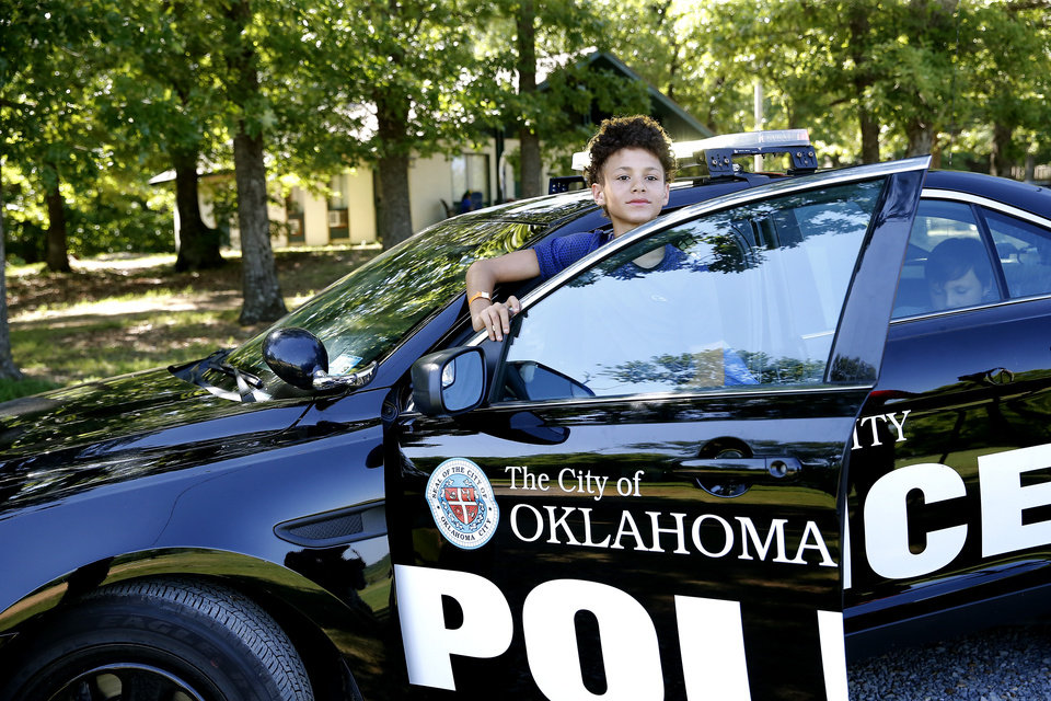 Photo -  A child uses the intercom on an Oklahoma City police car June 21 during Camp Hope in Chouteau. The camp is for children who have experienced trauma. [Photo by Sarah Phipps, The Oklahoman]