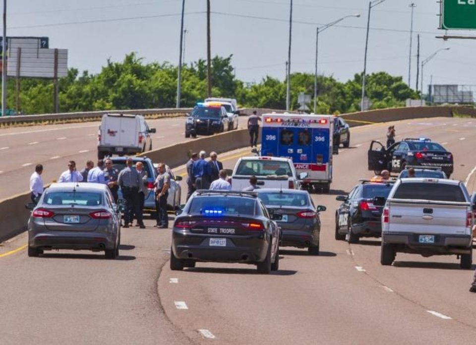 Photo -  Crews work the scene a fatal officer involved shooting on Interstate 35 in Oklahoma City on Monday. [Chris Landsberger/The Oklahoman]
