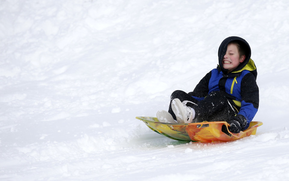 Photo - Jace Enright sleds on a hill along Hefner Road in Oklahoma City, Wednesday, Feb. 17, 2021. [Sarah Phipps/The Oklahoman]