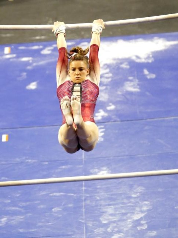 Photo -  OU's Anastasia Webb performs on the uneven bars Sunday at Lloyd Noble Center in Norman. [Sarah Phipps/The Oklahoman]