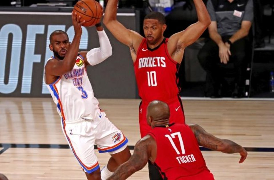 Photo -  Thunder guard Chris Paul (3) passes the ball away from Rockets guard Eric Gordon (10) and forward P.J. Tucker (17) during the first quarter of Game 2 on Thursday. [Kevin C. Cox/Pool Photo via AP]