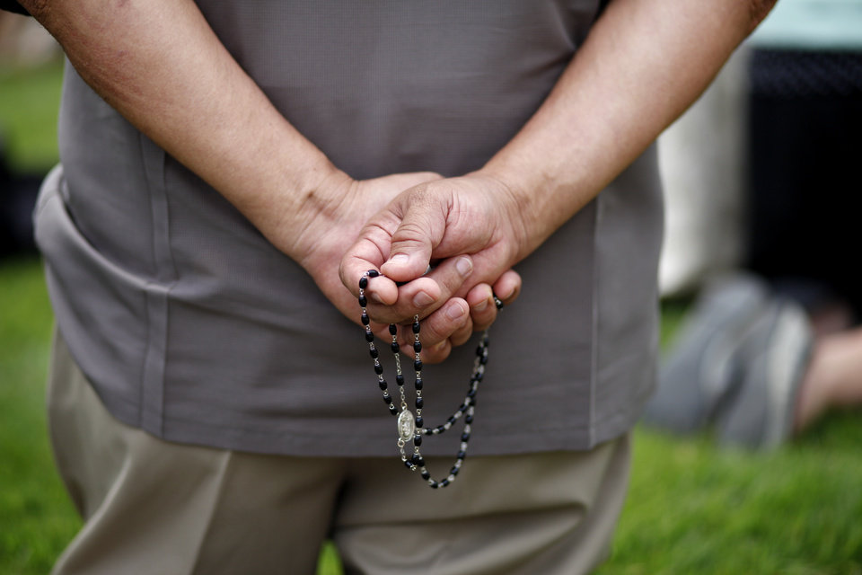 Photo - A man holds his rosary during a rosary procession in downtown Oklahoma City in protest of the Black Mass, Sunday, Sept. 21, 2014.  Photo by Garett Fisbeck, For The Oklahoman