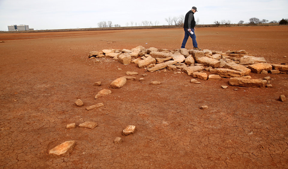 Photo -  David Gray steps across some of the concrete remains of the structures on the site of his grandmother's homestead, on what is now Lake Hefner. The lake has dropped so far that the foundation of her homestead is visible. Photo by Jim Beckel, The Oklahoman   Jim Beckel -  THE OKLAHOMAN