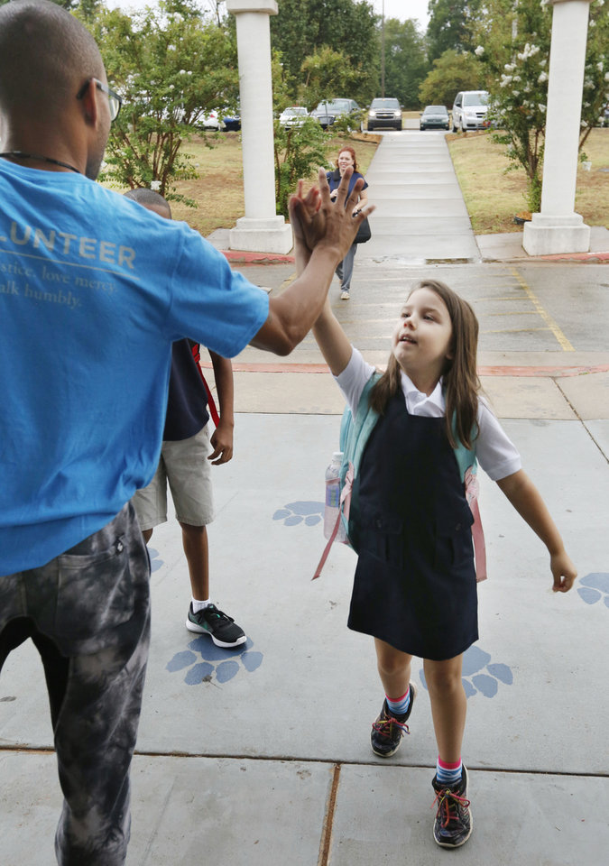Photo - Six year old Myrah Allen gives a high-five to volunteer Ernest Odunze at the beginning of the first day of school at Thelma Parks Elementary School in Oklahoma City, Okla. Tuesday, Aug. 1, 2017.  Photo by Paul Hellstern, The Oklahoman