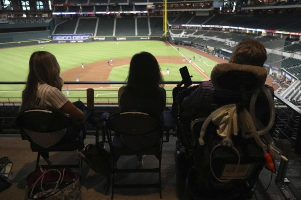 Photo -  Kat Minnerly, Tamara Hilliard, and Jim Hilliard watch the Colorado Rockies play against the Texas Rangers in an exhibition baseball game Tuesday in Arlington, Texas. [AP Photo/Richard W. Rodriguez]