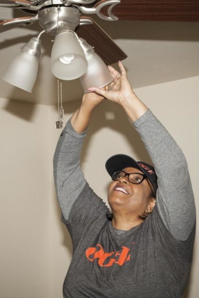 Photo -  Sharlett Combs, a volunteer with Oklahoma Gas and Electric Co., installs LED lighting at a home in the Mount Olive Senior Cottages development on Monday.