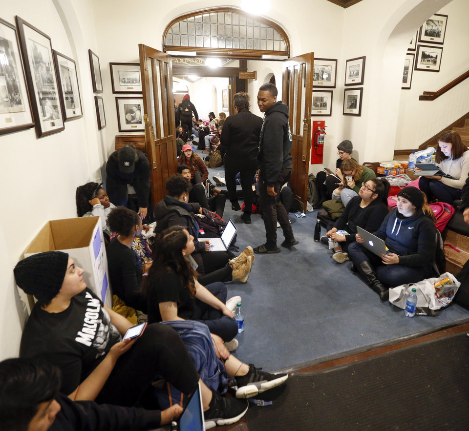 Photo - OU students and others line the hallways on the first floor of Evans Hall as they participate in a sit-in organized by the Black Emergency Response Team student group outside of the office of OU provost Kyle Harper at the University of Oklahoma in Norman, Okla., Wednesday, Feb. 26, 2020. The protest comes after two incidents where faculty members used a racial slur while teaching. [Nate Billings/The Oklahoman]