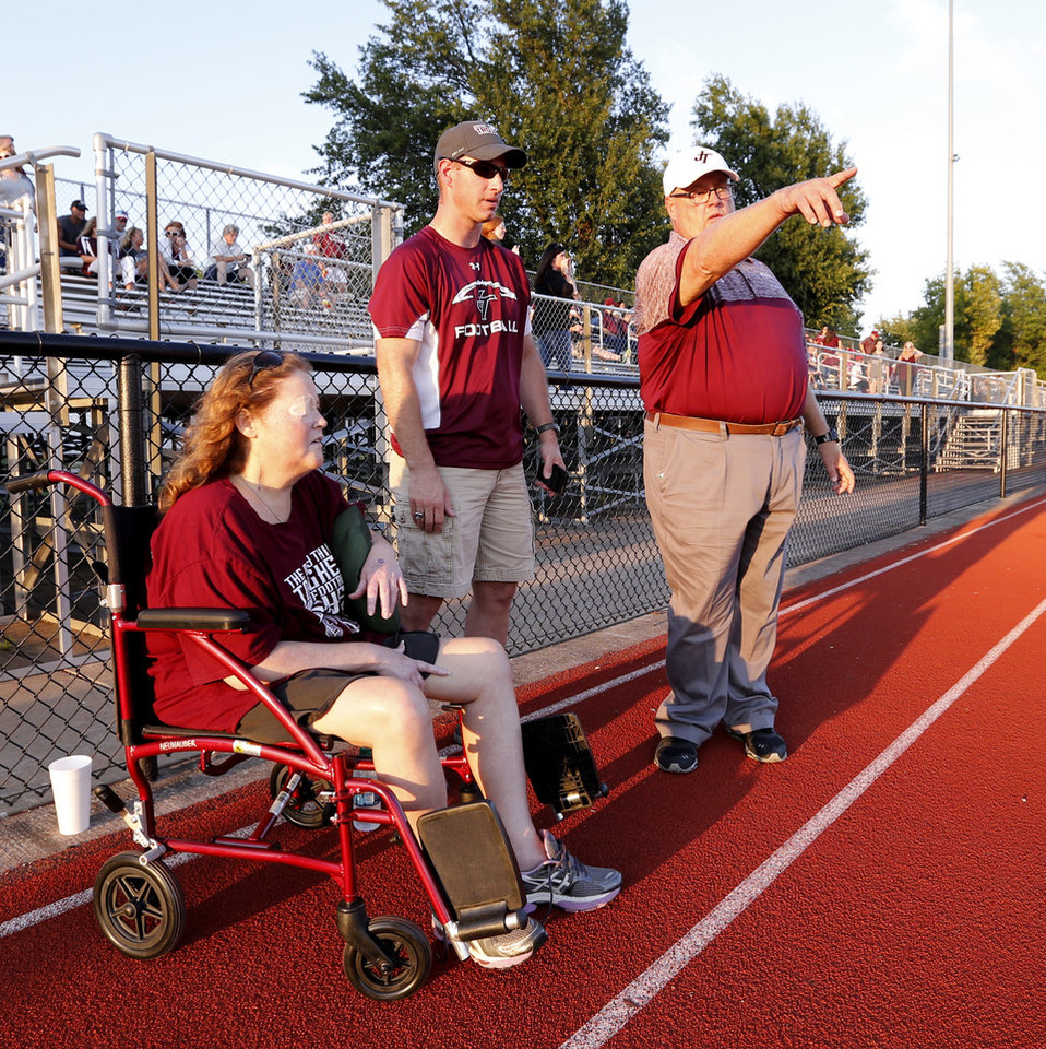 Photo - Jenks head coach Allan Trimble shows Tim and Gina Neuhauser where their son kicker Austin Neuhauser will kick off as he prepares his Jenks Trojans to play the Norman High School Tigers on Friday, Sept. 23, 2016 in Norman, Okla. Photo by Steve Sisney, The Oklahoman