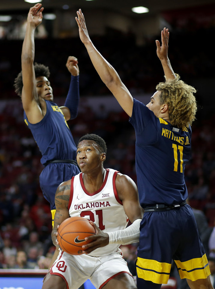 Photo - Oklahoma's Kristian Doolittle (21) looks to the basket from between West Virginia's Miles McBride (4) and Emmitt Matthews Jr. (11) during an NCAA mens college basketball game between the University of Oklahoma Sooners (OU) and the West Virginia Mountaineers at the Lloyd Noble Center in Norman, Okla.,Saturday, Feb. 8, 2020. Oklahoma won 69-59. [Bryan Terry/The Oklahoman]