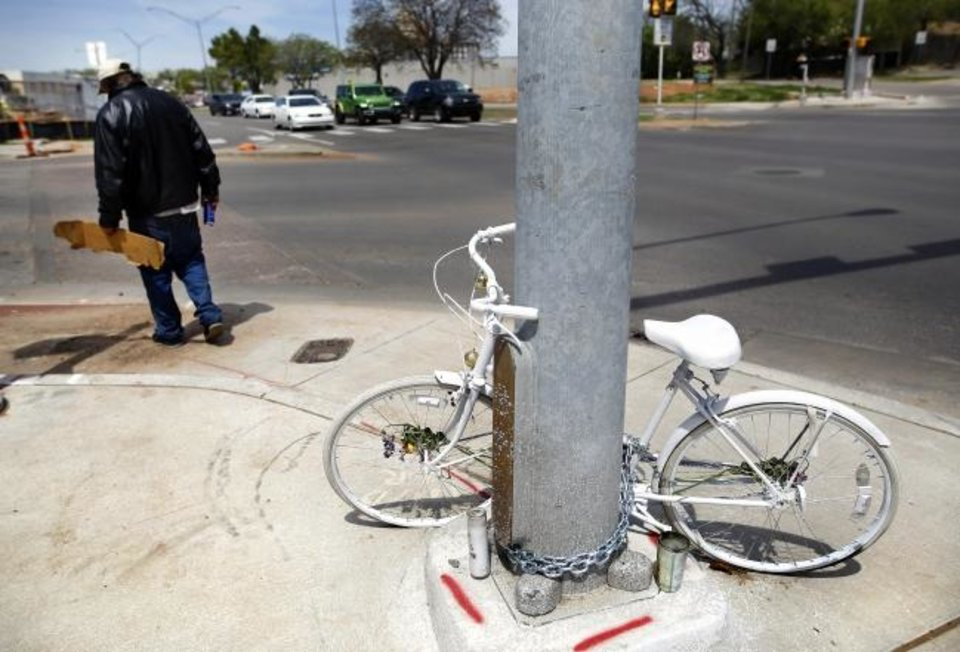 Photo -  A bicycle, painted white in its entirety, is chained to a pole at the intersection of NW 16 and Classen where Chad Epley was killed in March after being hit by a vehicle while biking home from work at a local restaurant. Classen is six lanes wide and cycling proponents want to see such streets made safer for pedestrians and cyclists. [JIM BECKEL/THE OKLAHOMAN]