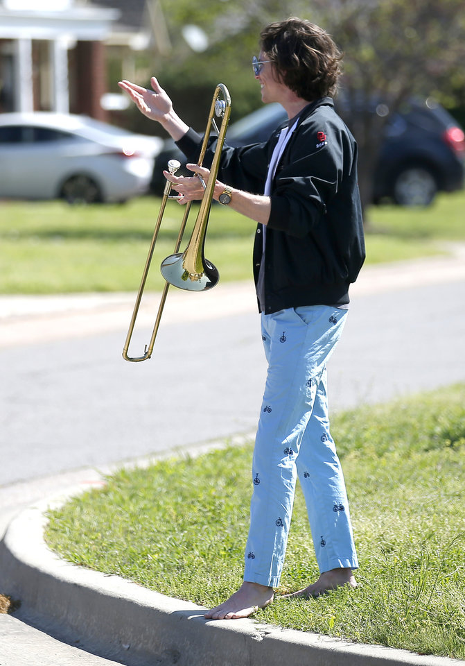 Photo - Christian Pearson acknowledges applause from neighbors after playing his trombone in Oklahoma City, Friday, April 10, 2020. [Sarah Phipps/The Oklahoman]
