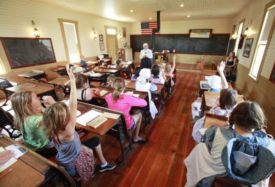 Photo - Children raise their hands to ask questions Wednesday during 1889 Summer Camp at Edmond's historic school house. PHOTO BY DAVID MCDANIEL, THE OKLAHOMAN  David McDaniel