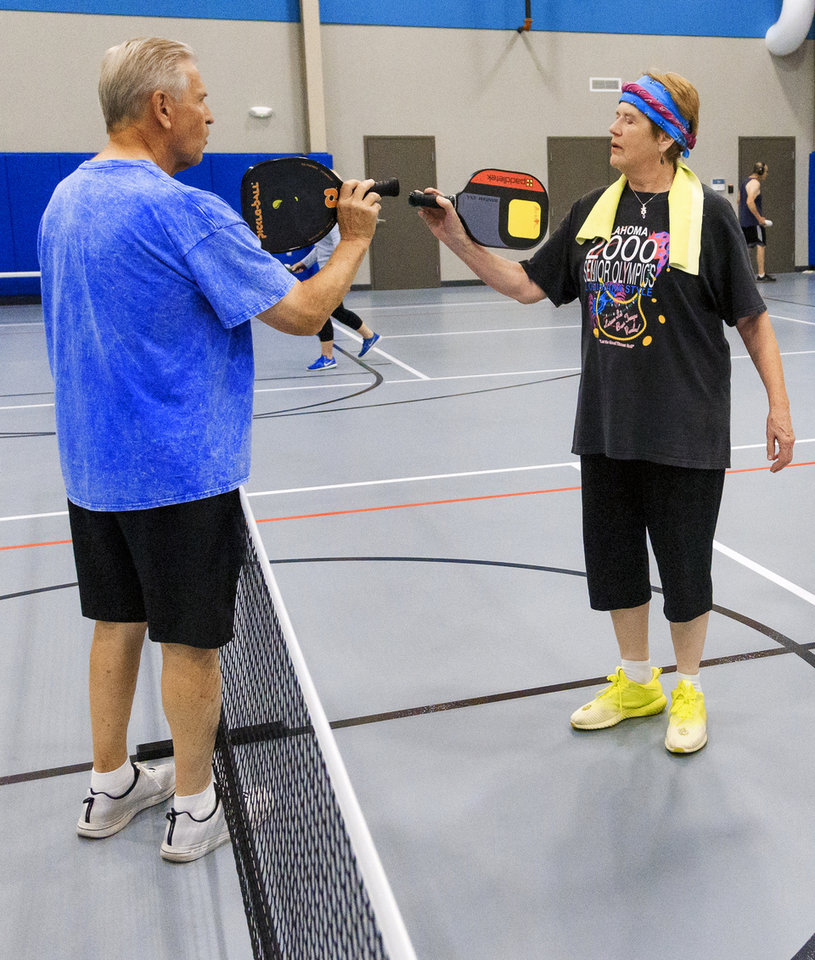 Photo -  Ardith Phares congratulates John Clements after a game of pickle ball. [PHOTO BY CHRIS LANDSBERGER, THE OKLAHOMAN]