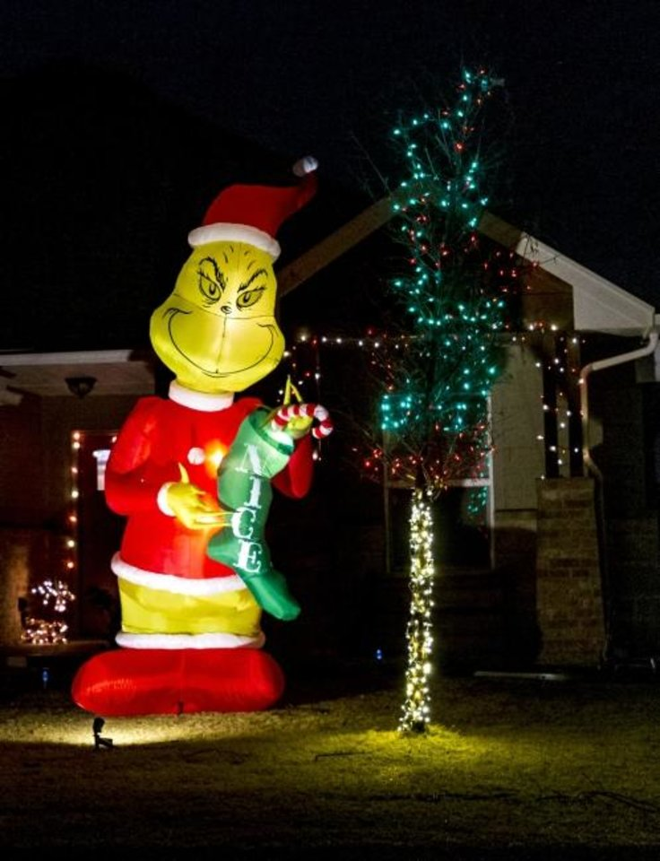 Photo -  The Grinch is among the Christmas decorations at 2208 Rivera Road in Yukon. [CHRIS LANDSBERGER/THE OKLAHOMAN]