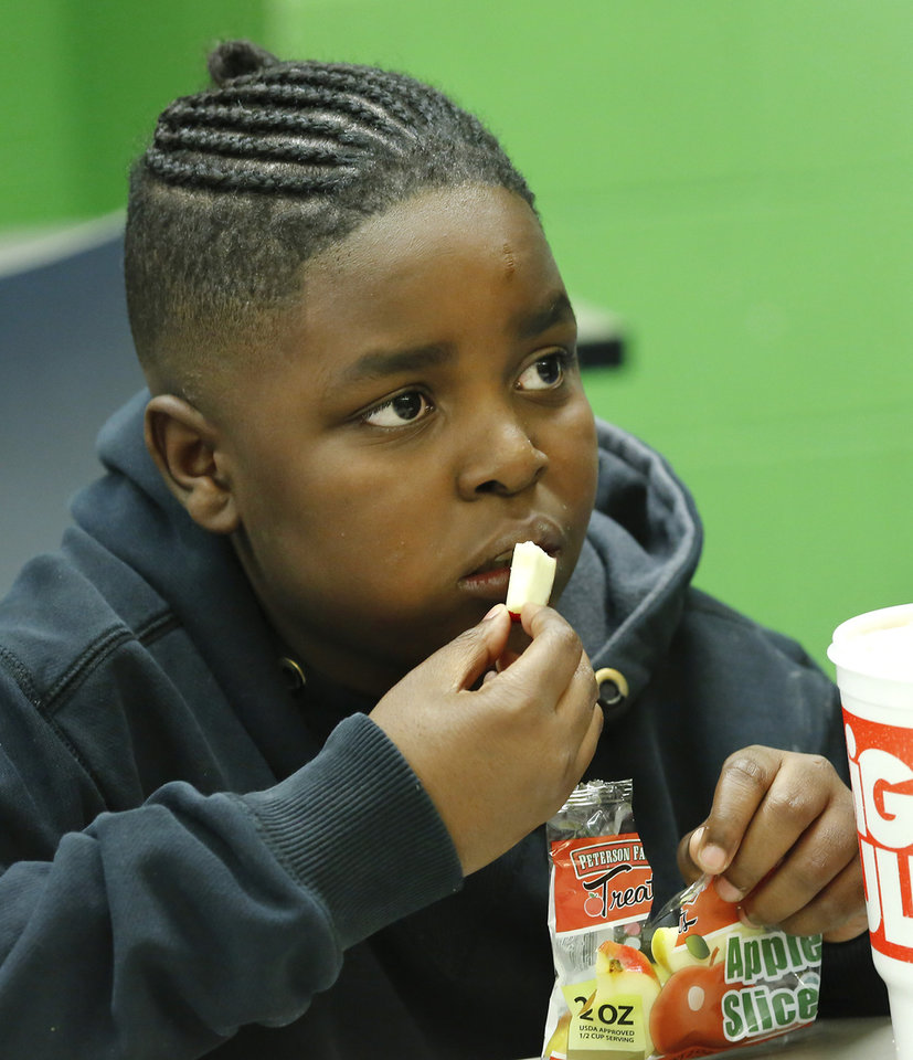 Photo - Student Jurney Ware eats apple slices  from his sack lunch given to them at a food truck provided by Oklahoma City Public Schools Nutrition Services on Monday, April 2, 2018. As a result of the teacher walkout, children who spent their day at the Boys and Girls Club of Oklahoma County  received free lunches from the school district. Photo by Jim Beckel, The Oklahoman