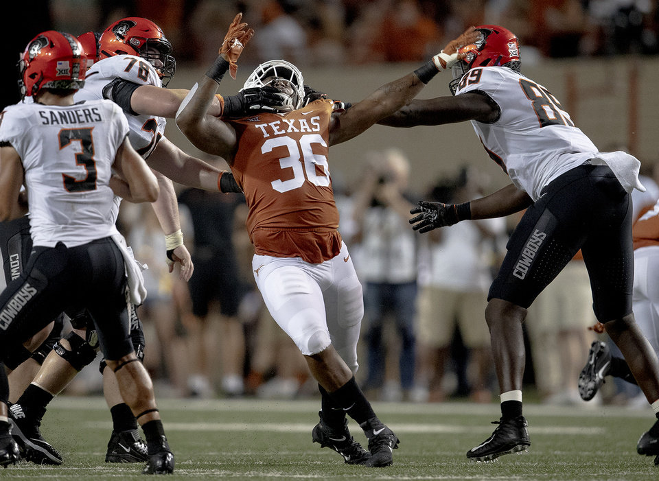 Photo - Oklahoma State offensive lineman Bryce Bray (78) and tight end Jelani Woods (89) block Texas defensive lineman Jacoby Jones (36) during an NCAA college football game Saturday, Sept. 21, 2019, in Austin, Texas. (Nick Wagner/Austin American-Statesman via AP)