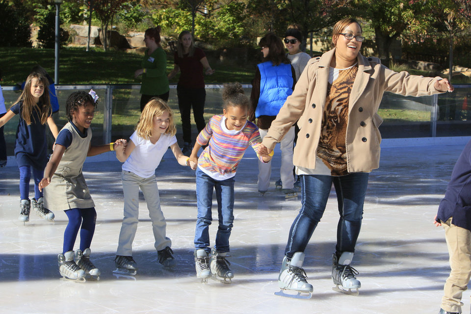 Photo - John Rex Charter school parent Nina Lofties guides her daughter Shylo and classmates Bella Weese-Woffard and Alivia Ward during the opening day of the Devon Ice Rink in downtown Oklahoma City, OK, Friday, November 13, 2015,  Photo by Paul Hellstern, The Oklahoman