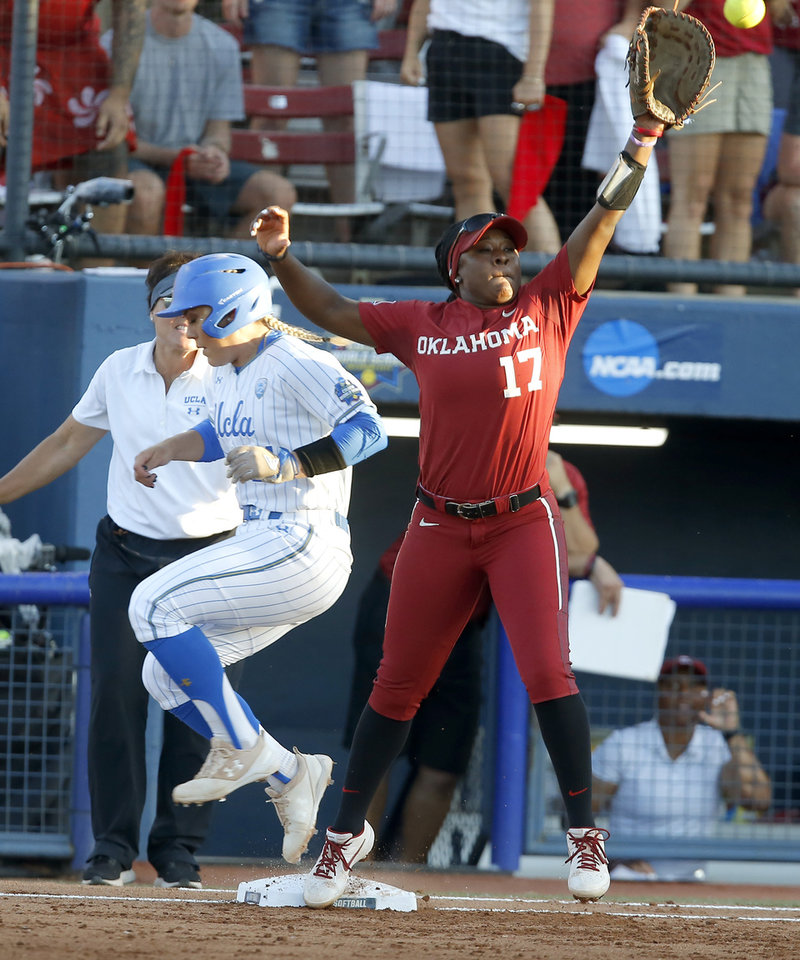 Photo - UCLA's Taylor Pack (21) is safe at first as Oklahoma's Shay Knighten (17) reaches for the ball in the first inning of the second NCAA softball game in the championship series of the Women's College World Series between Oklahoma and UCLA at USA Softball Hall of Fame Stadium in Oklahoma City, Tuesday, June 4, 2019. [Bryan Terry/The Oklahoman]