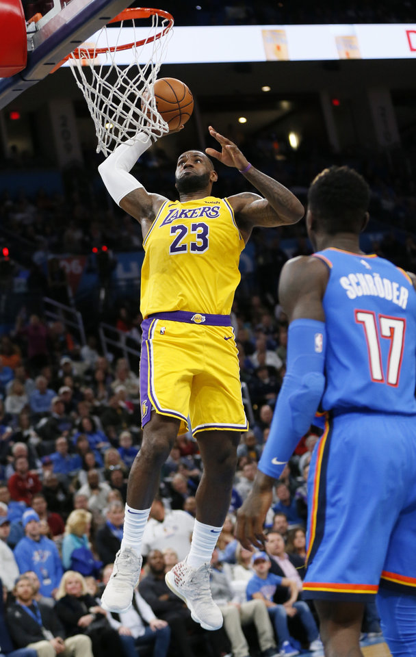 Photo - Los Angeles' LeBron James (23) dunks the ball in front of Oklahoma City's Dennis Schroder (17) in the third quarter during an NBA basketball game between the Oklahoma City Thunder and the Los Angeles Lakers at Chesapeake Energy Arena in Oklahoma City, Friday, Nov. 22, 2019. The Lakers won 130-127. [Nate Billings/The Oklahoman]