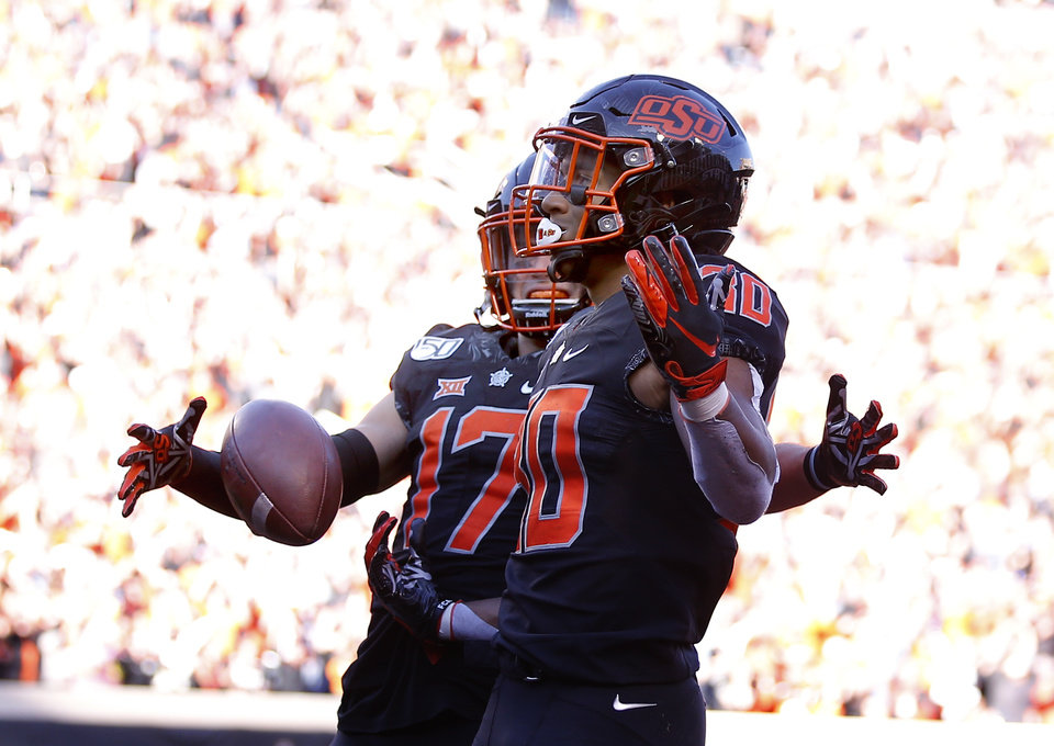 Photo - Oklahoma State's Chuba Hubbard (30) celebrates his 92-yard touchdown run with Dillon Stoner (17) in the third quarter during the college football game between the Oklahoma State University Cowboys and the TCU Horned Frogs at Boone Pickens Stadium in Stillwater, Okla.,  Saturday, Nov. 2, 2019. OSU won 34-27. [Sarah Phipps/The Oklahoman]