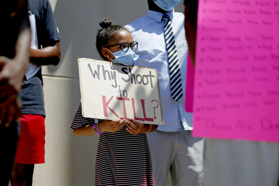 Photo - Bryanna Blue, 9, holds a sign during a protest in front of the Edmond Police Department in Edmond, Okla., Saturday, June 6, 2020. The protest was organized in response to the shooting death of Isaiah Lewis by Edmond Police last year and the death of George Floyd in Minneapolis. [Bryan Terry/The Oklahoman]