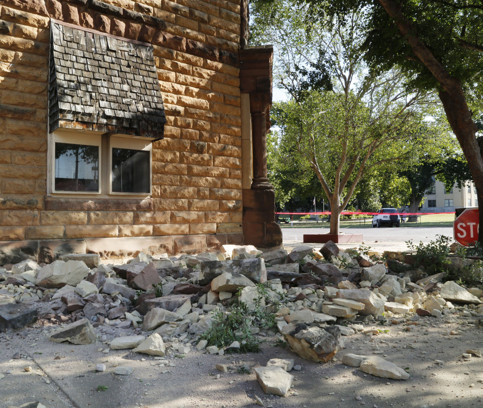 Photo - Sandstone bricks from the side of the historic Pawnee County Bank litter the sidewalk at Sixth St. and Harrison in Pawnee, Okla., after an early morning 5.6 magnitude earthquake struck, Saturday, Sept. 3, 2016.  Photo by Paul Hellstern, The Oklahoman