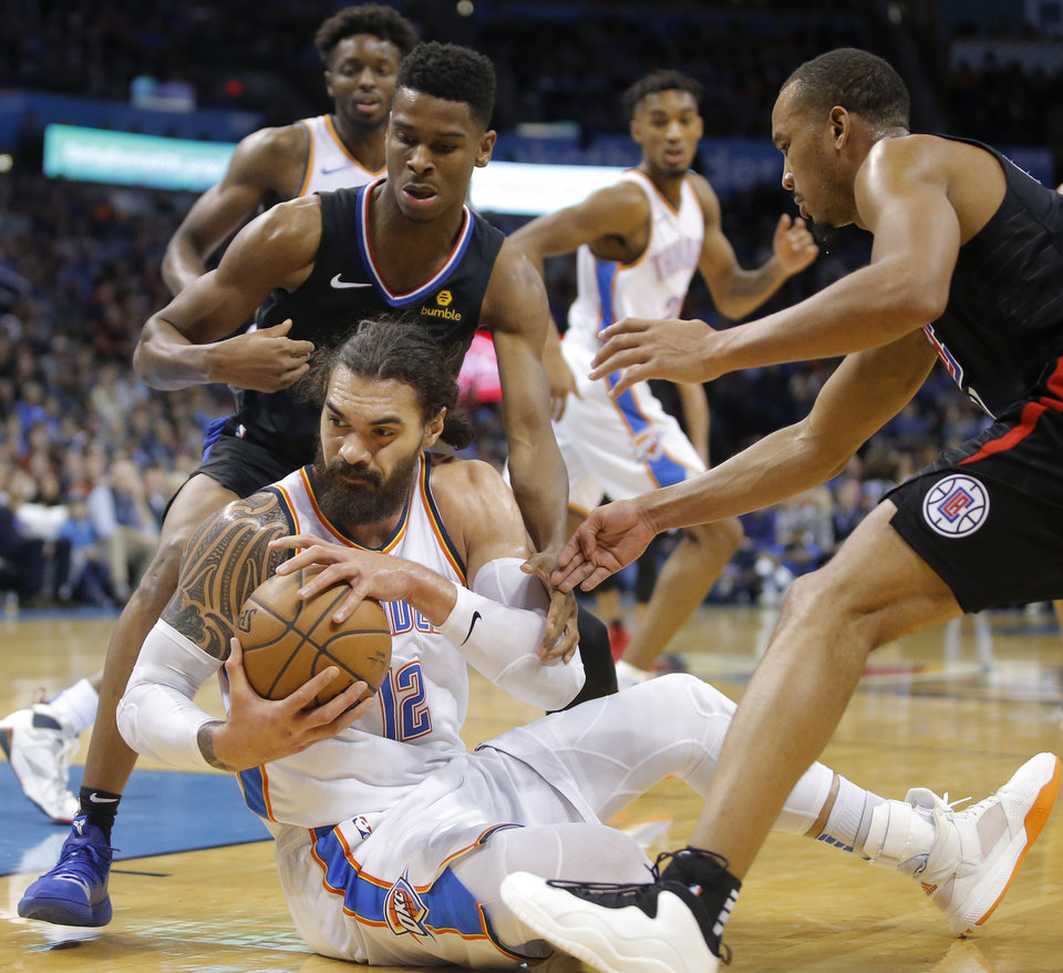 Photo - Oklahoma City Thunder's Steven Adams (12) tries to gain control of the ball between Shai Gilgeous-Alexander (2) and Avery Bradley (11) of the Los Angeles Clippers during an NBA basketball game between the Oklahoma City Thunder and the Los Angeles Clippers at Chesapeake Energy Arena in Oklahoma City, Saturday, Dec. 15, 2018. Oklahoma City won 110-104. Photo by Bryan Terry, The Oklahoman