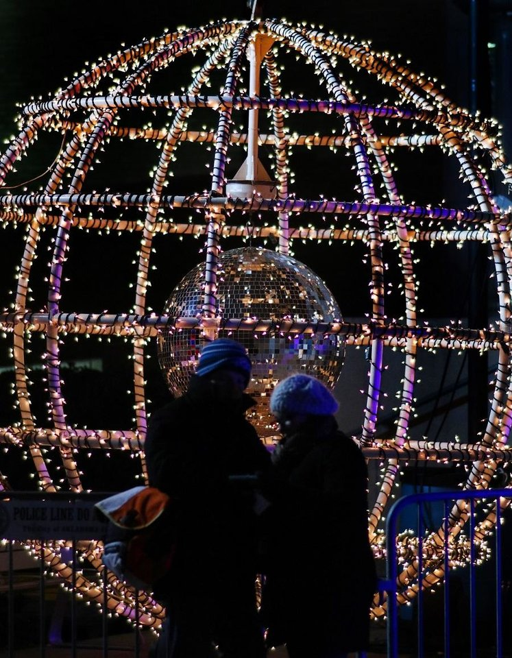 Photo - A couple stops in front of the giant, light-adorned ball at Opening Night 2019 in Bicentennial Park in downtown Oklahoma City, Monday, December 31, 2018. The ball raises for the countdown to midnight every year as part of the New Year's Eve festivities. [Doug Hoke/ The Oklahoman Archives]