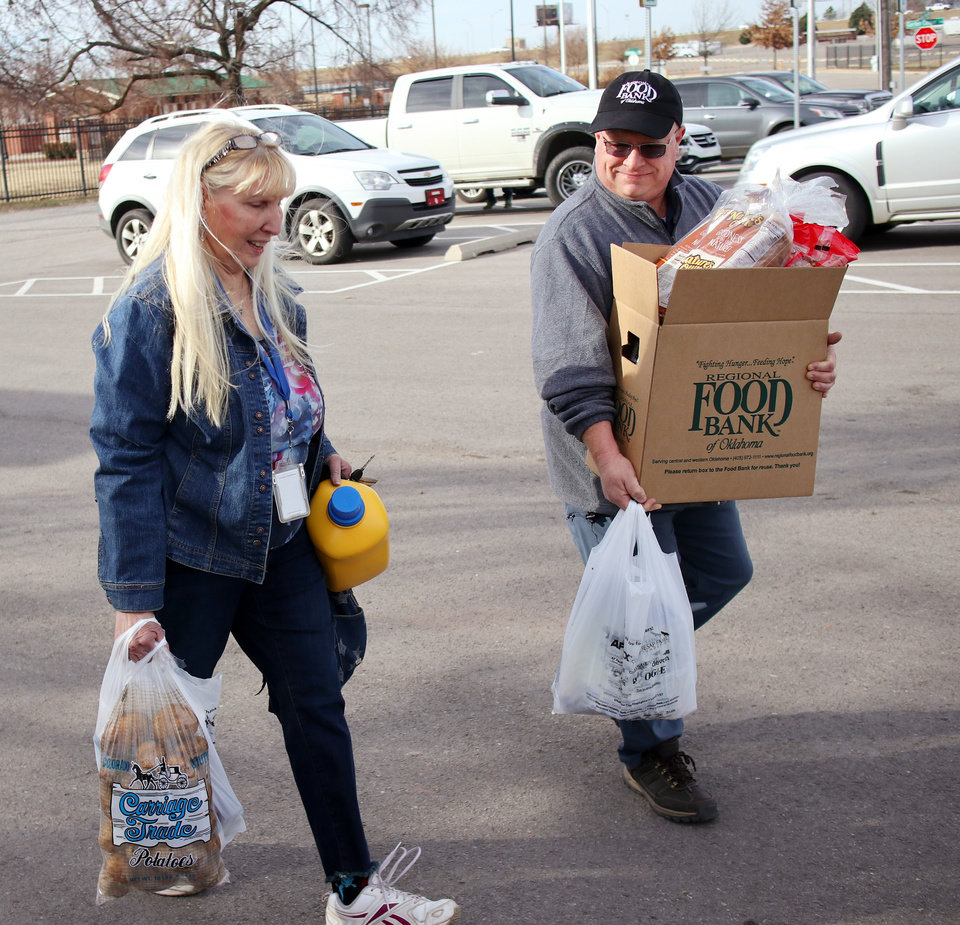 Photo - Volunteer John Mankin helps Betty Robins, who works at FAA, carry food to her vehicle, during a free food distribution for federal employees by the Regional Food Bank of Oklahoma at State Fair Park Monday, January 21, 2019.  Photo by Doug Hoke, The Oklahoman