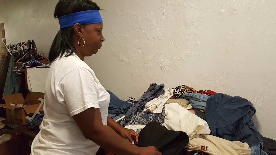 Photo - Volunteer Janet Sanders, a VA Medical Center employee, straightens clothing during a clothes giveaway held as part of the Helping Hands 10th anniversary celebration on Aug. 27 at The Christ Experience, 1006 NE 17. [Photo by Carla Hinton, The Oklahoman]