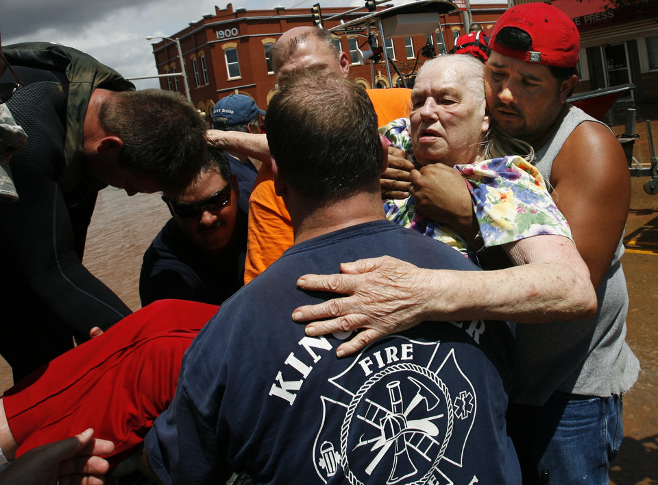 Photo - Margaret Free is lifted from an rescue boat on Sunday, August 19, 2007, in Kingfisher, Okla. By James Plumlee, The Oklahoman.