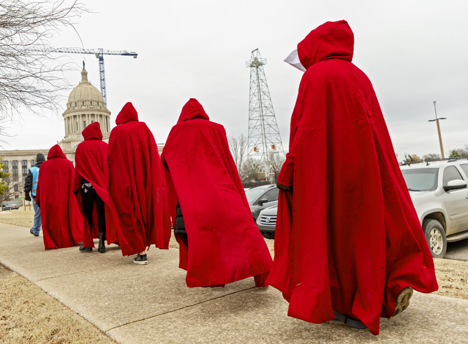 Photo - Pro-Choice supporters dressed in handmaid attire walk to the State Capitol as they take part in a Pro-Choice  rally against Senate Bill 13 that would abolish abortion in the state of Oklahoma at the State Capitol in Oklahoma City, Okla. on Tuesday, Feb. 11, 2020.  [Chris Landsberger/The Oklahoman]