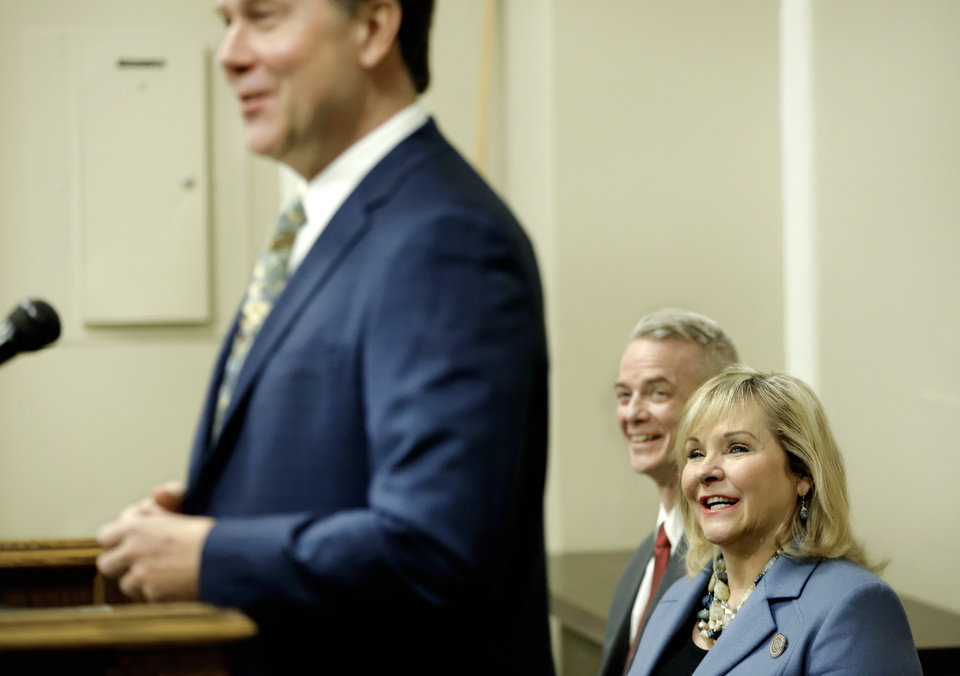 Photo - Gov. Mary Fallin and US Rep. Steve Russell, seated in background, laugh as they listen to remarks from Steve Fendley, president of Kratos Unmanned Systems Division at Friday's news conference. US Congressman Steve Russell joined Gov. Mary Fallin at the state Capitol on Friday, Jan. 26, 2018, to announce a company that produces high performance, jet-powered unmanned aerial tactical and target drone systems will open an office in Oklahoma. The state officials, including Vince Howie, aerospace and defense director for Oklahoma, Kratos Defense and Security Solutions, Inc. plans to open administrative and engineering offices and production facilities in Oklahoma City. Photo by Jim Beckel, The Oklahoman