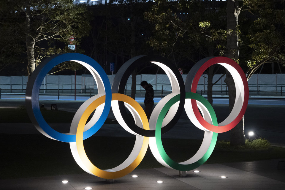 "Photo - A man is seen through the Olympic rings in front of the New National Stadium in Tokyo, Tuesday, March 24, 2020. IOC President Thomas Bach has agreed ""100%"" to a proposal of postponing the Tokyo Olympics for about one year until 2021 because of the coronavirus outbreak, Japanese Prime Minister Shinzo Abe said Tuesday. (AP Photo/Jae C. Hong)"