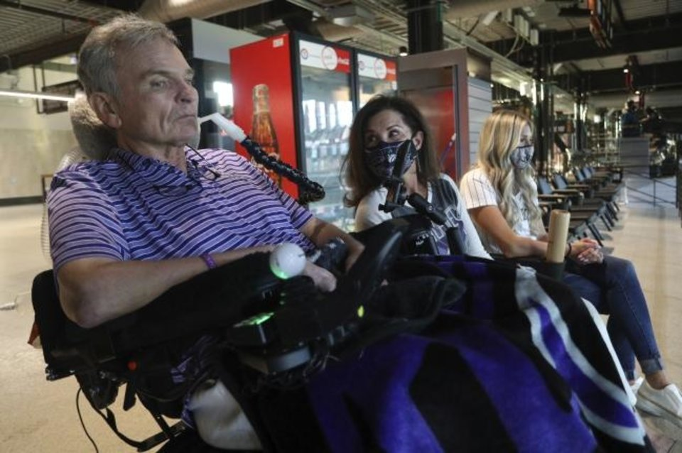 Photo -  Jim Hilliard, Tamara Hilliard and Kat Minnerly watch the Colorado Rockies play against the Texas Rangers in an exhibition baseball game Tuesday in Arlington, Texas. [AP Photo/Richard W. Rodriguez]