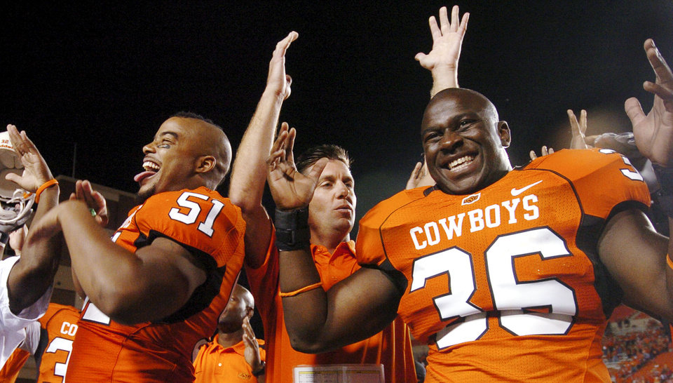 Photo - OSU defensive end Victor DeGrate (51) left, head coach Mike Gundy, center, and linebacker Alex Odiari, (36) right, raise their arms to make the letter