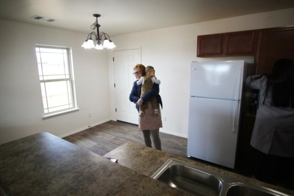 Photo -  Brittani Githiri holds her one year old son, Piaget, as she looks around the finished house for the first time. [Doug Hoke/The Oklahoman]