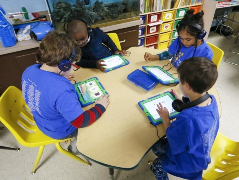 Photo -  Clockwise from left, kindergartener John, 6,  first-grader Chance, 7, kindergartener Lilly, 6, and kindergartener James, 5, use tablets at Positive Tomorrows school for homeless children in Oklahoma City, Wednesday, Jan. 23, 2019. Photo by Nate Billings, The Oklahoman