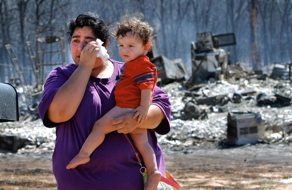 Photo -  ictoria Landavazo holds youngest child, Axel, 1 year old, while wiping tears after arriving with other members of her family to see for the first time what the wildfire had done to their home. Victoria and her husband lived in the house with their seven children until yesterday when fire reduced it to charred rubble and hot ashes. They had lived there for two years. Residents  in Luther were allowed to return to the their homes early Saturday, Aug. 4, 2012, after they fled a rapidly moving wildfire yesterday that consumed at least seven structures on South Dogwood Street, leaving smoldering ashes where family homes once stood.    Photo by Jim Beckel, The Oklahoman.