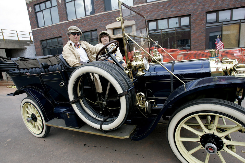 Photo - Ed Baldwin of Oklahoma City with his son Luke drive a 1910 Packard in the Oklahoma Centennial Parade Saturday, Oct. 14, 2007. He drove the parade route twice the first time carrying the Gov.'s family and then the three Heisman trophy winners.  BY JACONNA AGUIRRE/THE OKLAHOMAN.